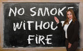 Teacher showing No smoke without fire on blackboard — 图库照片