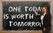 Profesor mostrando uno hoy vale dos mañana en pizarra — Foto de Stock