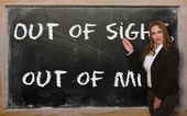 Teacher showing Out of sight, out of mind on blackboard — Photo