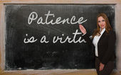 Teacher showing Patience is a virtue on blackboard — Stock Photo