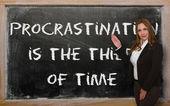 Teacher showing Procrastination is the thief of time on blackboa — Stock Photo