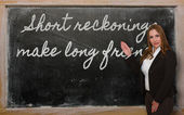 Teacher showing Short reckonings make long friends on blackboard — Stockfoto