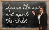 Teacher showing Spare the rod and spoil the child on blackboard — Stock Photo
