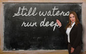 Teacher showing Still waters run deep on blackboard — 图库照片