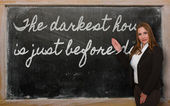 Teacher showing The darkest hour is just before dawn on blackboa — ストック写真