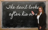 Teacher showing The devil looks after his own on blackboard — Stok fotoğraf