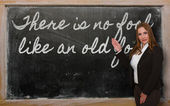 Teacher showing There is no fool like an old fool on blackboard — ストック写真