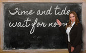 Teacher showing Time and tide wait for no man on blackboard — Stockfoto