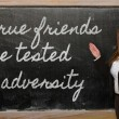 Stock Photo: Teacher showing True friends are tested in adversity on blackboa