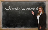 Teacher showing Time is money on blackboard — Stockfoto