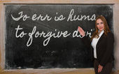 Teacher showing To err is human, to forgive divine on blackboard — Stock Photo