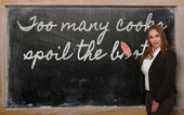 Teacher showing too many cooks spoil the broth on blackboard — Stockfoto