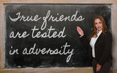 Teacher showing True friends are tested in adversity on blackboa — Stock Photo