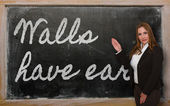 Teacher showing Walls have ears on blackboard — Stock Photo