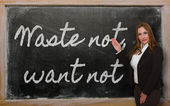 Teacher showing Waste not, want not on blackboard — Stockfoto