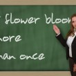Teacher showing A flower blooms more than once on blackboard — Stock Photo