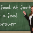 Foto Stock: Teacher showing fool at forty is fool forever on blackboard