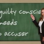 Teacher showing A guilty conscience needs no accuser on blackboa — Stock Photo