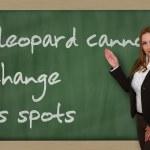 Teacher showing A leopard cannot change its spots on blackboard — Stock Photo #25996371