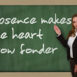 Teacher showing Absence makes heart grow fonder on blackboar — Stock Photo #25997881
