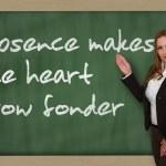 Teacher showing Absence makes the heart grow fonder on blackboar — Stock Photo #25997881