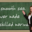 Teacher showing A smooth sea never made a skilled mariner on bla — Stock Photo
