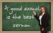 Teacher showing A good example is the best sermon on blackboard — Stock Photo