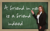Teacher showing A friend in need is a friend indeed on blackboar — Stock Photo