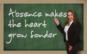 Teacher showing Absence makes the heart grow fonder on blackboar — Stock Photo