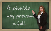 Teacher showing A stumble may prevent a fall on blackboard — Stock Photo