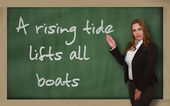 Teacher showing A rising tide lifts all boats on blackboard — Stockfoto