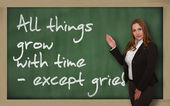 Teacher showing All things grow with time - except grief on blac — Stock Photo