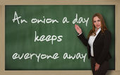 Teacher showing An onion a day keeps everyone away on blackboard — Stock Photo