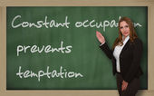 Teacher showing Constant occupation prevents temptation on black — Stock Photo