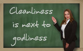 Teacher showing Cleanliness is next to godliness on blackboard — Stock Photo