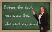 Teacher showing Better the devil you know than the devil you on — Stock Photo