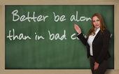 Teacher showing Better be alone than in bad company on blackboar — Stock Photo