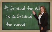 Teacher showing A friend to all is a friend to none on blackboar — Stock Photo
