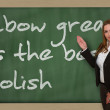 Teacher showing Elbow grease is best polish on blackboard — Stock Photo #26010297