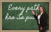 Teacher showing Every path has its puddle on blackboard — Stock Photo
