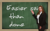 Teacher showing Easier said than done on blackboard — Stock Photo