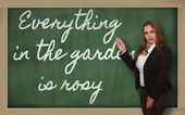 Teacher showing Everything in the garden is rosy on blackboard — Stock Photo