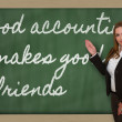 Teacher showing Good accounting makes good friends on blackboard — Stock Photo #26024673