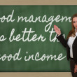 Stock Photo: Teacher showing Good management is better than good income on bl