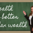 Teacher showing Health is better than wealth on blackboard — Stock Photo #26026379