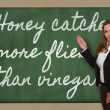 Teacher showing Honey catches more flies than vinegar on blackbo — Stock Photo #26026775