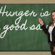 Teacher showing Hunger is a good sauce on blackboard — Stock Photo #26026999