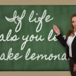 Teacher showing If life deals you lemons, make lemonade on black — Stock Photo