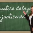 Teacher showing Justice delayed is justice denied on blackboard — Stock Photo