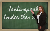 Teacher showing Facts speak louder than words on blackboard — Foto Stock